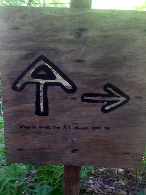 "A sign on the trail indicating a turn, with the accurate graffiti, ""When in doubt, the A.T. always goes up."""