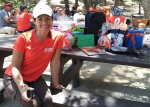 Laura wearing her orange in front of the prizes she collected for the hikers